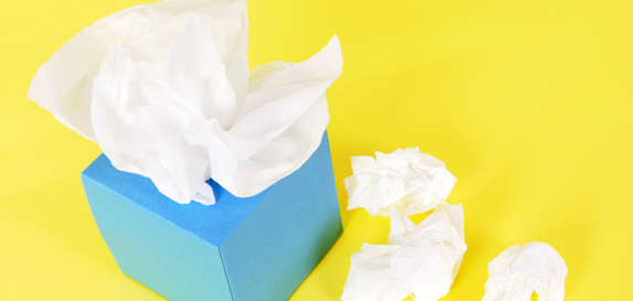 A blue box of tissues sits near crumpled tissue on a bright yellow background.