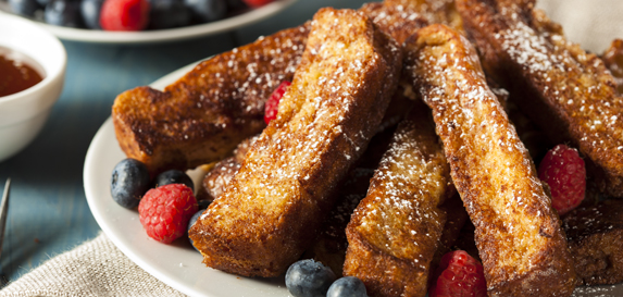 French toast cut into slices are piled on a white plate with blueberries and red raspberries as garnish. A bowl of blueberries and red raspberries are in the background.