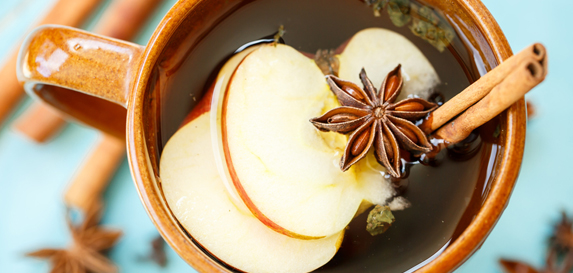 Hot spiced cider fills a brown mug and contains slices of apples, accompanied by cinnamon sticks and star anise seed.