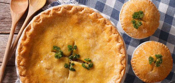 A large chicken pot pie and two small chicken pot pies sit on a white and blue gingham patterned table cloth.