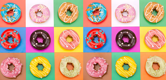 3 repeating rows of 6 multi-colored donuts on a gridded background